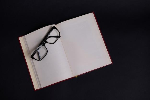 Lay piatto di occhiali su un libro aperto con copertina rigida rossa, isolato su sfondo nero con spazio per il testo. concetto del giorno dell'insegnante, conoscenza, letteratura, lettura, erudizione