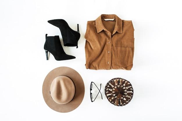 Collage di moda piatto laici con abiti e accessori moderni da donna su superficie bianca