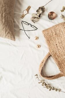 Accessori moda donna piatti laici: occhiali, orologio, orecchini, borsa di paglia, cuscino, rami di eucalipto su lino bianco