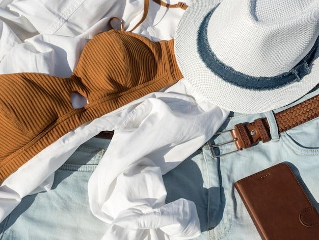 Accessori da spiaggia per donna estate moda piatta laici: reggiseno, camicia, cappello, cintura, smartphone. sfondo di vacanza di viaggio.