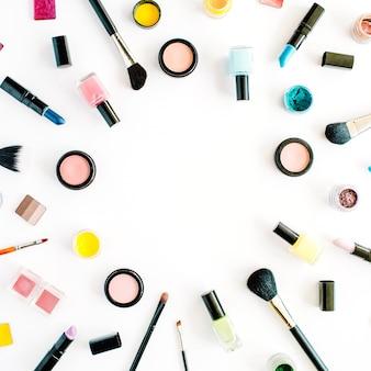 Cornice di collage di cosmetici femminili piatti laici con rossetto, pennello su bianco