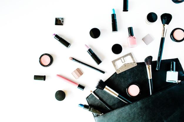 Collage di cosmetici femminili piatti laici con rossetto, pennello su bianco
