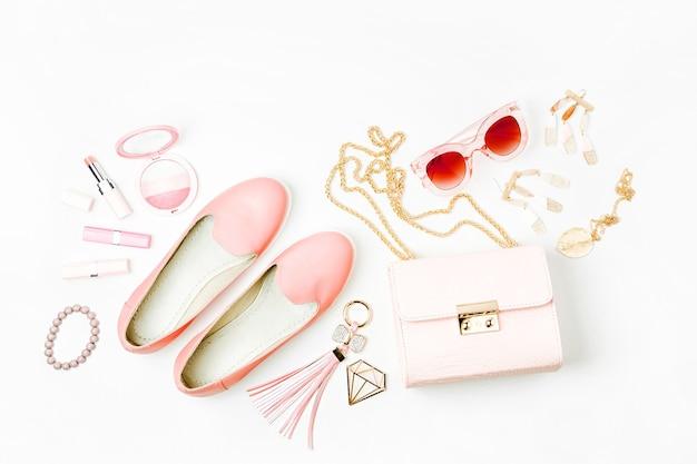 Disposizione piana di accessori di moda femminile, scarpe, prodotti per il trucco e borsetta su sfondo color pastello. concetto di bellezza e moda