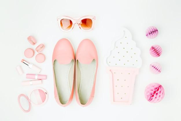 Disposizione piatta di accessori di moda femminile, scarpe, prodotti per il trucco su sfondo color pastello. concetto di bellezza e moda