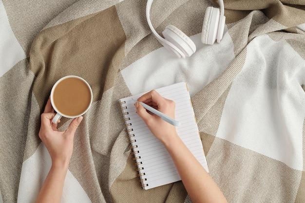 Piatto laici delle mani femminili con la penna sulla pagina vuota del taccuino e la tazza di cappuccino fresco rendendo note di lavoro o piano in pausa