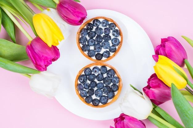 Piatto flatlay laici in alto sopra close up foto di bellissimi gustosi dessert deliziosi sulla piastra con cornice floreale isolato superficie di colore pastello