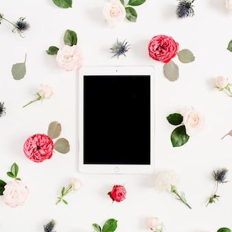 Cornice floreale piatta con tablet, boccioli di fiori rosa rossi e beige su sfondo bianco. vista dall'alto