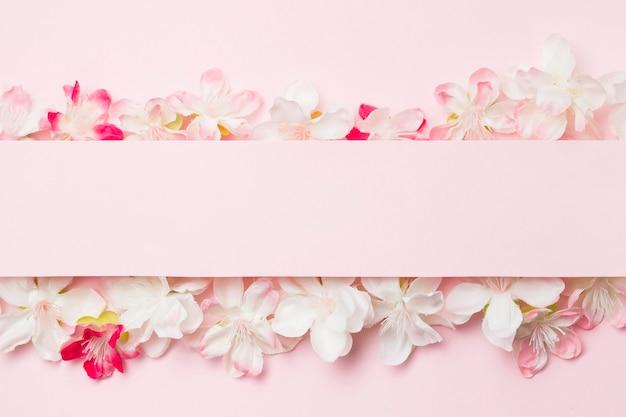 Fiori piatti laici su sfondo rosa con carta bianca