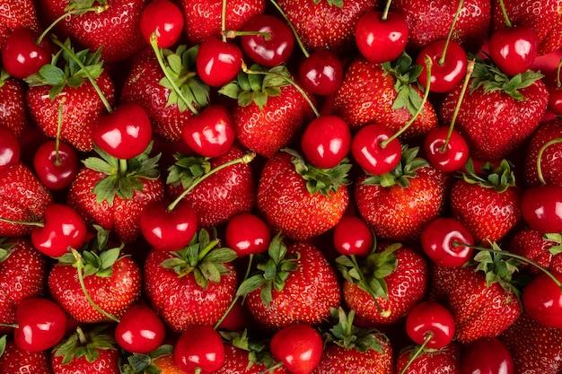 Fondo fresco piatto, fragole e ciliegie appena raccolte, fondo con frutti di bosco e frutti di stagione.