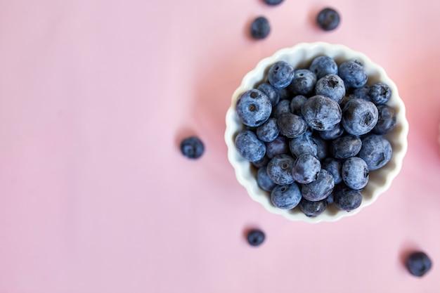 Disposizione piana dei mirtilli succosi organici freschi in una ciotola su fondo rosa, vista superiore, spazio della copia. concetto di alimentazione sana e dietetica, antiossidante, vitamina, cibo estivo.