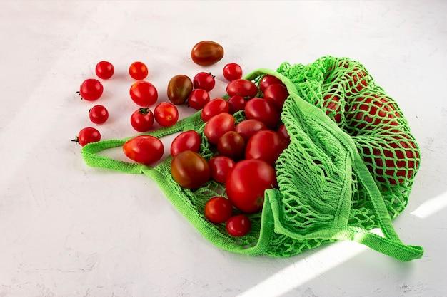Pomodoro fresco piatto laico in sacchetto della spesa riutilizzabile eco con rete senza spreco su bianco