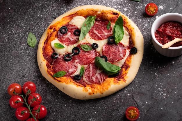 Lay piatto di pizza appena sfornata con olive e basilico e ingredienti su uno sfondo nero