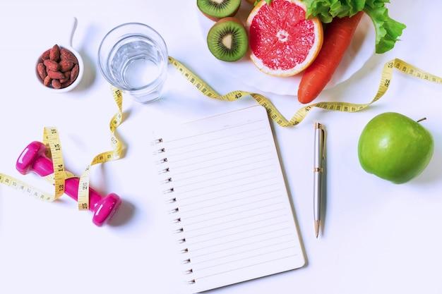 Piatto disteso di frutta, verdura, manubri, metro a nastro e un bicchiere d'acqua
