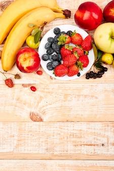 Disposizione piana dei frutti sopra fondo di legno bianco