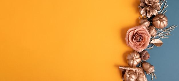 Disposizione piatta di ghiande dorate, coni, foglie e zucche su uno sfondo colorato. concetto di autunno minimalista con copia spazio. formato banner