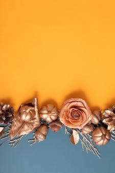 Disposizione piatta di ghiande dorate, coni, foglie e zucche su uno sfondo colorato. concetto di autunno minimalista con copia spazio. formato verticale
