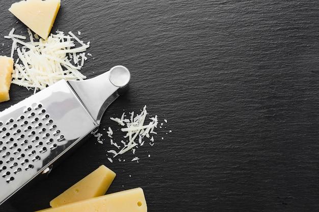 Parmigiano grattugiato piatto e grattugia con spazio di copia Foto Premium