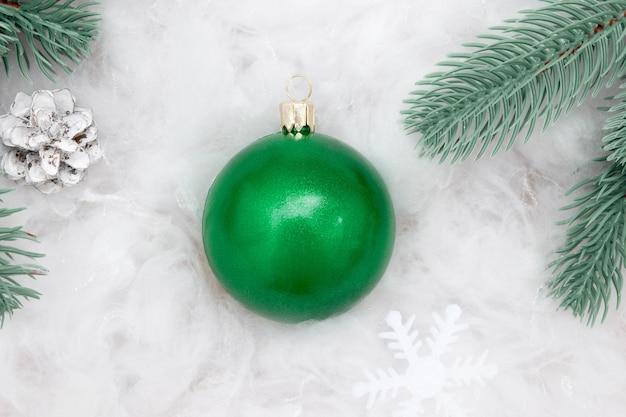 Mockup di palla di natale verde piatto laici su una neve