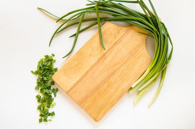 Piuma piana della cipolla verde di disposizione e pezzi affettati sul taglio del bordo di legno isolato, concetto dell'alimento biologico, spazio della copia