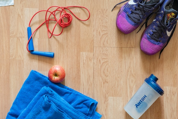 Attrezzature da palestra piatte come scarpe da ginnastica con corda per saltare e asciugamano con mela e gambe umane b