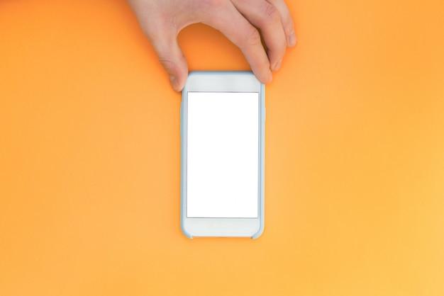 Mano piatta distesa con telefono. la mano tiene uno smartphone con uno schermo bianco su uno sfondo arancione.