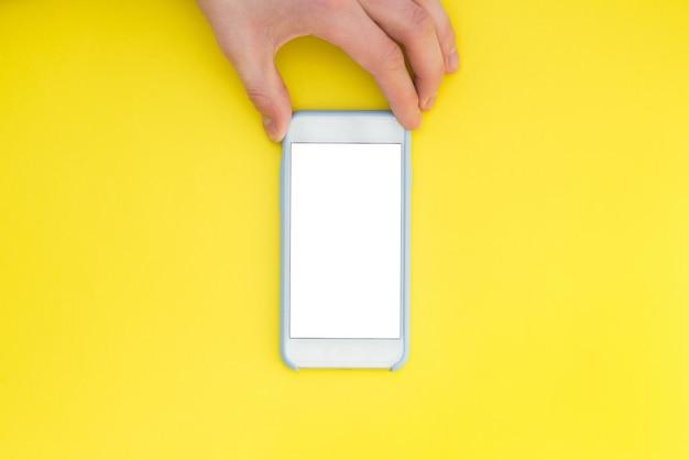Mano piatta distesa con telefono. la mano tiene uno smartphone con uno schermo bianco su uno sfondo giallo.
