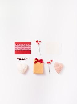 Lay piatto di buste fatte a mano, regalo, cuori, rose e piume per biglietto di auguri
