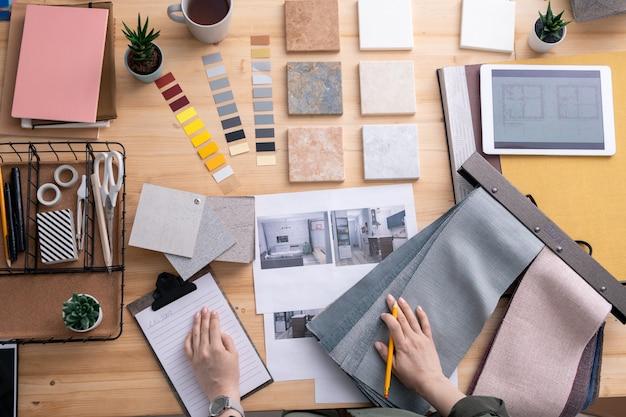 Piatto le mani del designer di interni creativo contemporaneo sul posto di lavoro durante il lavoro su un nuovo appartamento o una stanza in casa