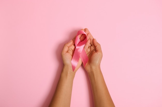 Disposizione piatta delle mani che tengono nastro rosa su sfondo rosa, consapevolezza del cancro al seno, ottobre pink day, world wancer way, national cancer survivor say. l'assistenza sanitaria delle donne e il concetto medico. copia spazio