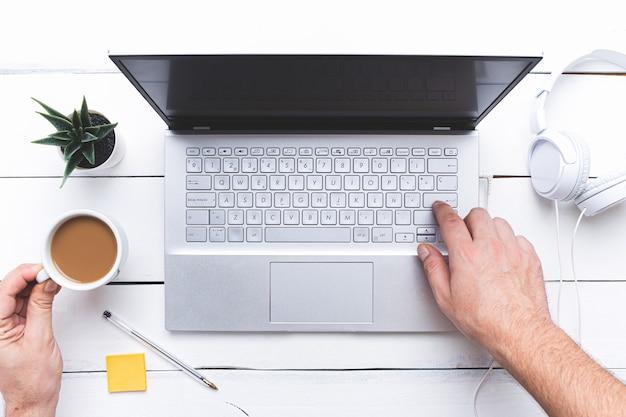 Piatto disteso, mani toccando una tastiera del computer portatile e tenendo una tazza di caffè sul tavolo di legno bianco.