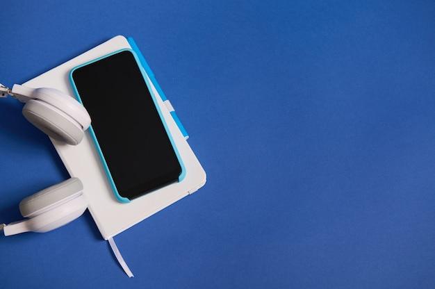 Cuffie piatte, smartphone in custodia blu su organizzatore di diario bianco isolato su sfondo blu con spazio di copia. vista dall'alto di strumenti per ufficio bicolore bianco e blu