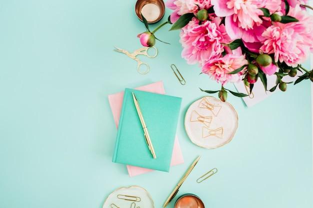 Scrivania da ufficio piatta. area di lavoro femminile con bouquet di fiori di peonia rosa, accessori dorati, diario rosa e menta sulla menta
