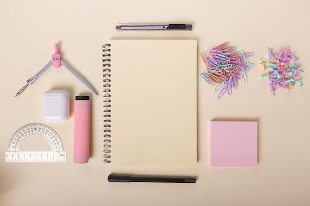 Flat lay home office scrivania blocco note bussole pennarello cuffie vista dall'alto righello scrivania da donna beauty conc...