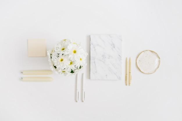 Scrivania da ufficio piatta. area di lavoro della donna con bouquet di fiori di camomilla e diario in marmo su bianco