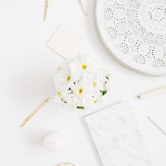 Scrivania da ufficio piatta. area di lavoro della donna con bouquet di fiori di camomilla su bianco