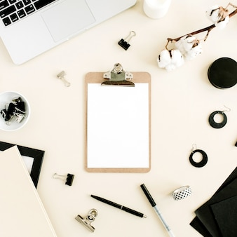 Scrivania da ufficio piatta. area di lavoro con appunti, laptop su sfondo beige pastello. vista dall'alto