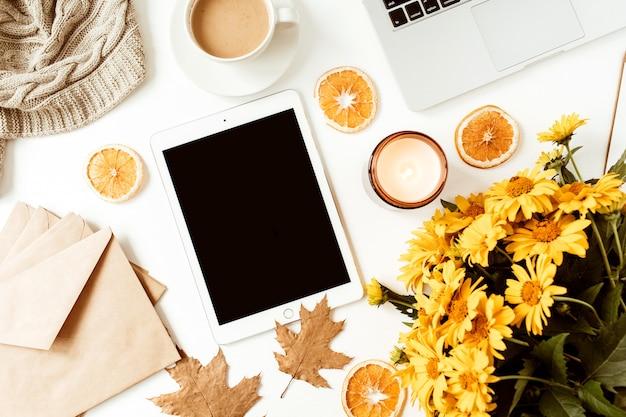 Area di lavoro piana della scrivania del tavolo dell'ufficio domestico della disposizione con il modello in bianco della compressa dello spazio della copia, il laptop, la tazza di caffè, la coperta, le buste, le foglie sulla superficie bianca