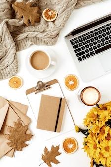 Area di lavoro della scrivania del tavolo da ufficio a casa piatta con laptop, appunti, bouquet di fiori, tazza di caffè, coperta, buste, foglie, fette d'arancia su bianco. vista dall'alto