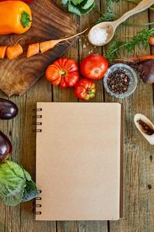 Disposizione piatta dell'ingrediente di cucina, verdure intorno al ricettario, drogheria, cibo locale, alimentazione sana e pulita, cibo vegetariano e vegano, concetto di primavera dietetica, vista dall'alto, spazio copia.