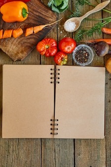 Lay piatto di ingrediente di cucina, verdure intorno al ricettario