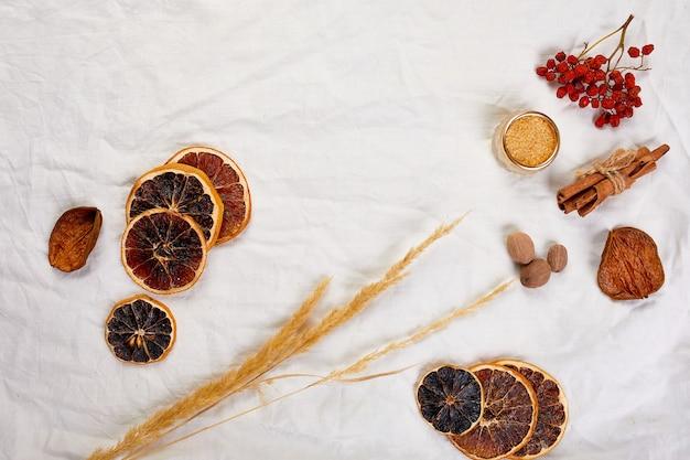Disposizione piatta di ingredienti e bottiglia di vino rosso per vin brulé stagionale invernale su tovaglia di lino tessile bianco, natura morta, sfondo trama panno, bevanda natalizia, spazio copia.