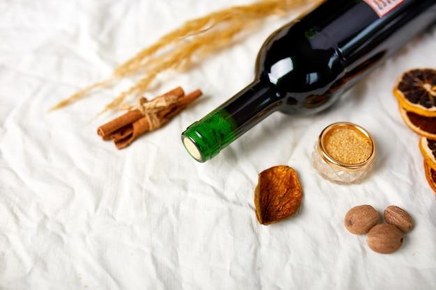 Disposizione piatta di ingredienti e bottiglia di vino rosso per vin brulè stagionale invernale