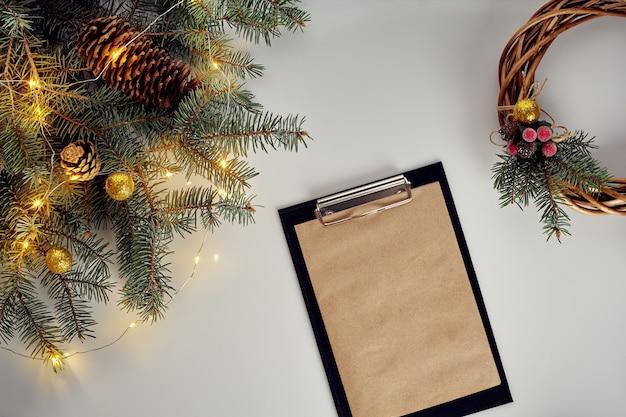 Disposizione piana dei rami di pino verde della corona di ginepro, della corona e della carta del mestiere sulla tavola bianca, vista superiore. preparazione per le vacanze di natale