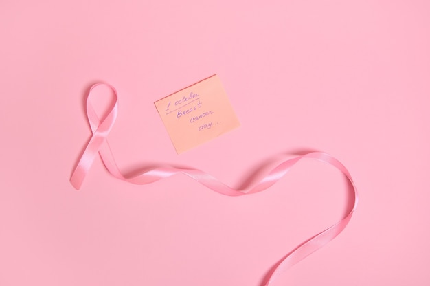 Disposizione piatta di un lungo nastro rosa con un'estremità infinita e una nota di carta con scritta 1 ottobre giornata di sensibilizzazione sul cancro al seno, isolata su sfondo rosa con spazio per il testo