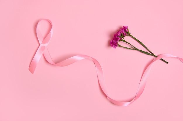 Disposizione piatta di un lungo nastro di raso rosa, dove un'estremità è infinita e fiori. consapevolezza del cancro al seno, concetto medico isolato su sfondo rosa con spazio di copia. campagna del mese di sensibilizzazione di ottobre.