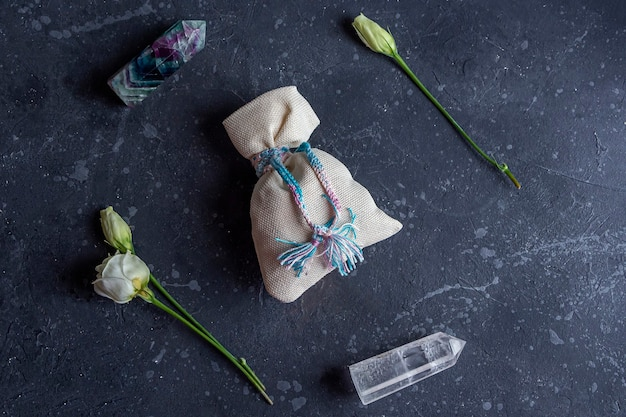 Composizione magica piatta con cristalli, borsa pagana e fiori di rosa