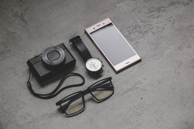 Lay piatto di accessori uomo su una superficie di cemento grigio