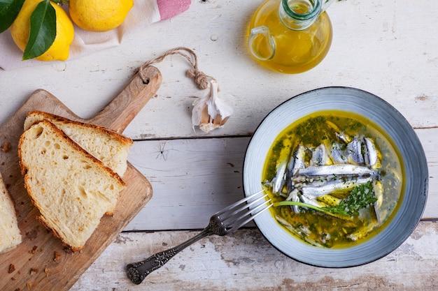 Piatto di acciughe marinate in succo di limone con olio d'oliva aglio e prezzemolo. piatti estivi mediterranei tradizionali