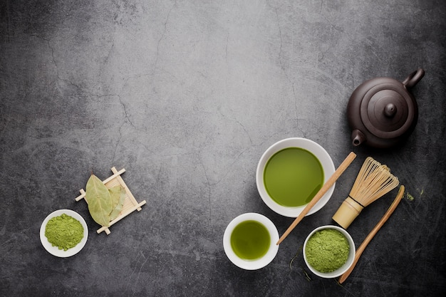 Lay piatto di tè matcha con frusta di bambù e copia spazio