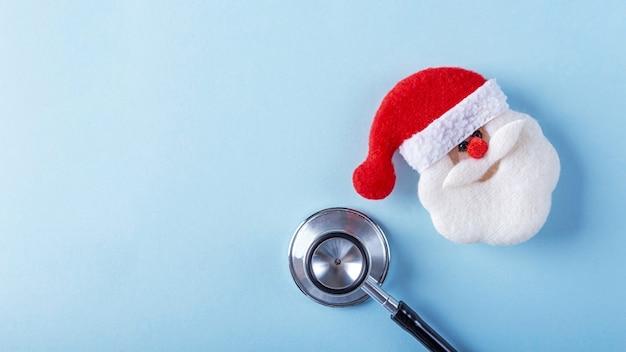 Composizione di natale medica piatta laici con lo stetoscopio e il giocattolo di babbo natale sull'azzurro